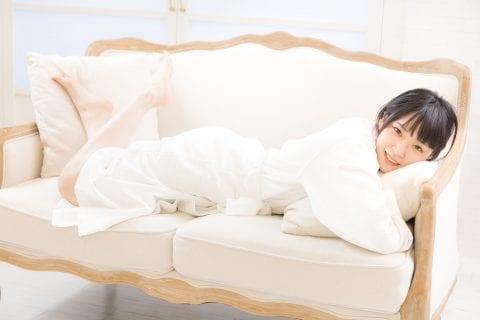 ソファに横たわり笑顔を見せている女性