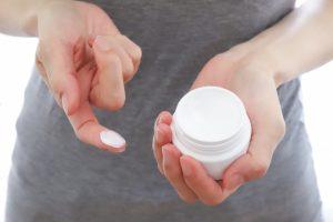手にクリームをつける女性